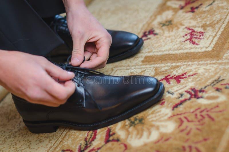 Mężczyzna stawia jego czerń buty Ręki przygotowywać w kostiumu mężczyzna dostaje fotografia stock