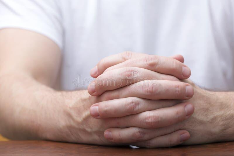 Mężczyzna stawia palce krzyżujących na stole fotografia stock