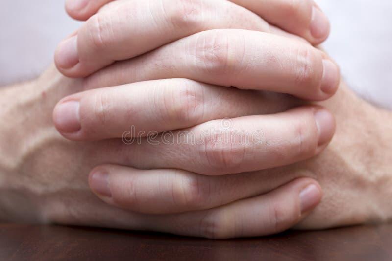Mężczyzna stawia palce krzyżujących na stole obraz stock