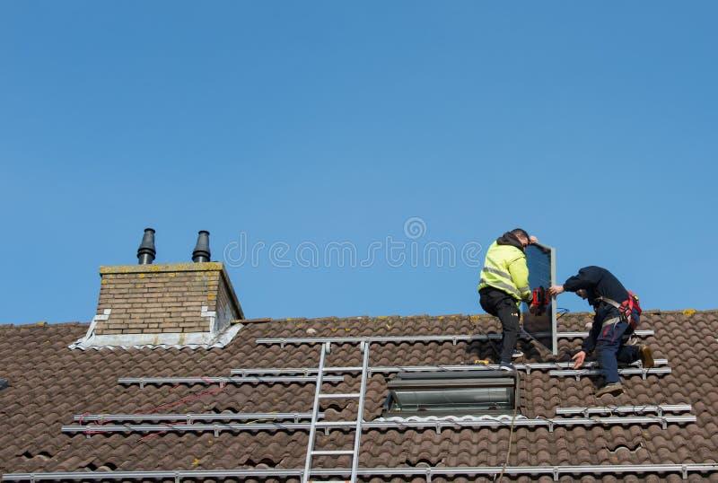 Mężczyzna stawia panelu słonecznego na dachu obrazy royalty free