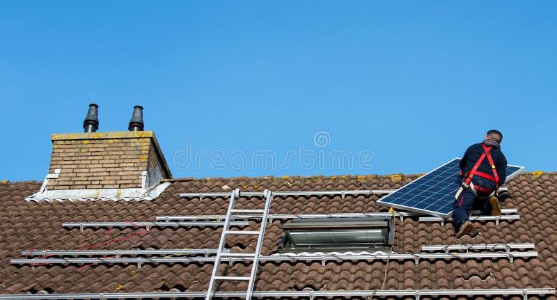 Mężczyzna stawia panelu słonecznego na dachu fotografia royalty free