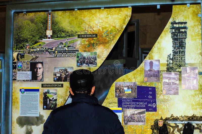 Mężczyzna stoi blisko fotografii nieboszczyka żołnierze, wojownicy Ukraiński wojsko w muzeum Anta Terrorystyczna operacja, obraz stock