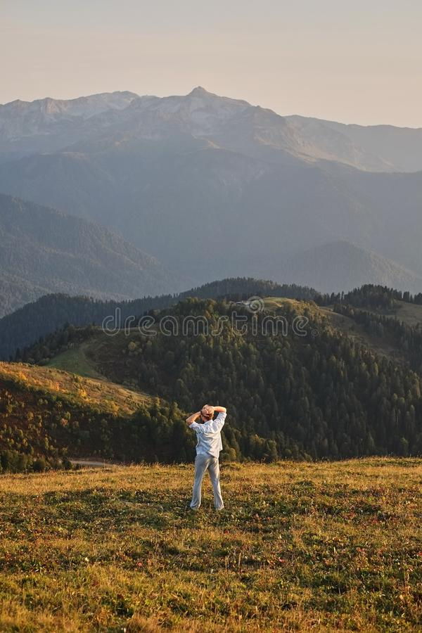 Mężczyzna stoi na szczycie faleza z jego plecy kamera, cieszy się scenicznego widok zielony las piękny mou i zdjęcie royalty free