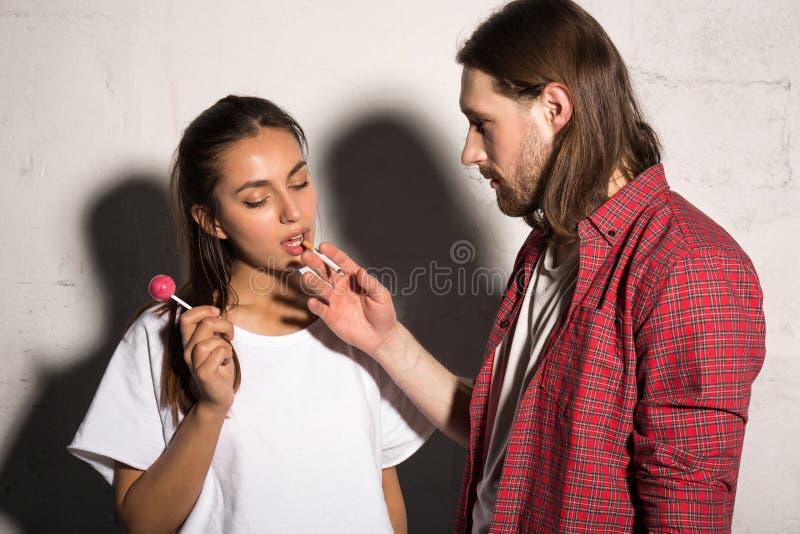 Mężczyzna stoi nad szarym tłem daje papierosowi dziewczyna fotografia stock