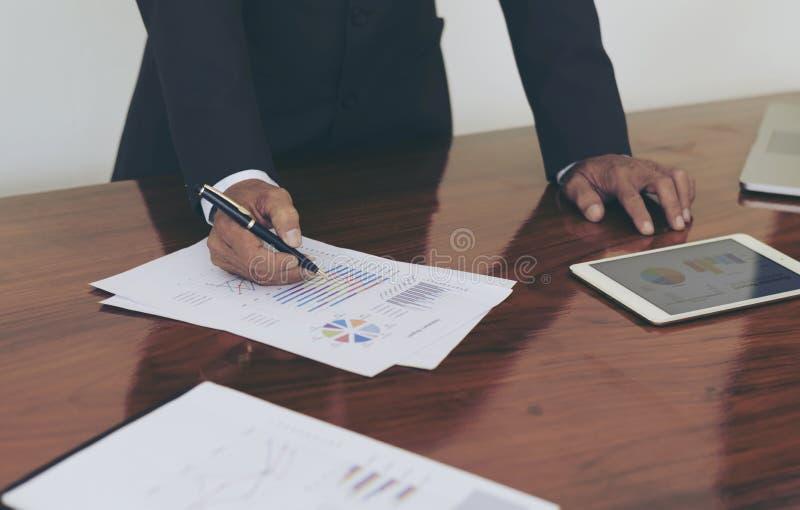 Mężczyzna stoi przy biurkiem i pracującym writing dokumentu ręki zakończeniem up zdjęcie royalty free