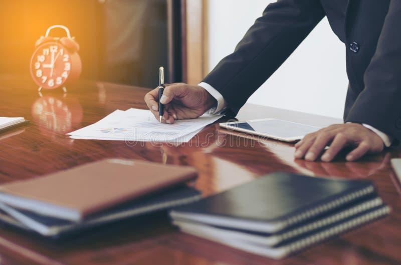 Mężczyzna stoi przy biurkiem i pracującym writing dokumentu ręki zakończeniem up obrazy stock