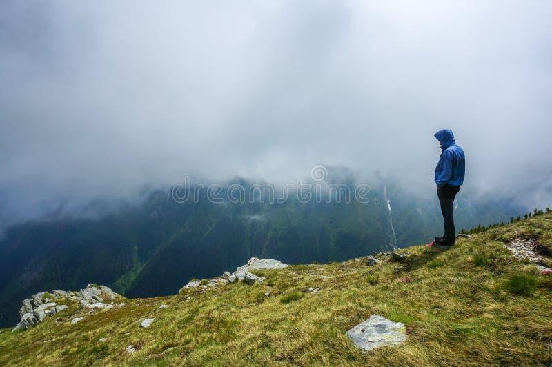 Mężczyzna stoi samotnie w górach zdjęcia stock