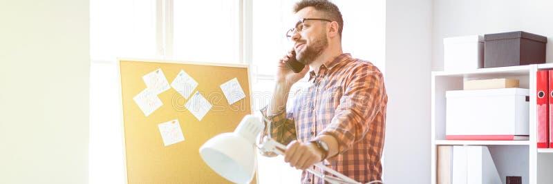 Mężczyzna stoi w biurze blisko okno i opowiada na telefonie fotografia royalty free