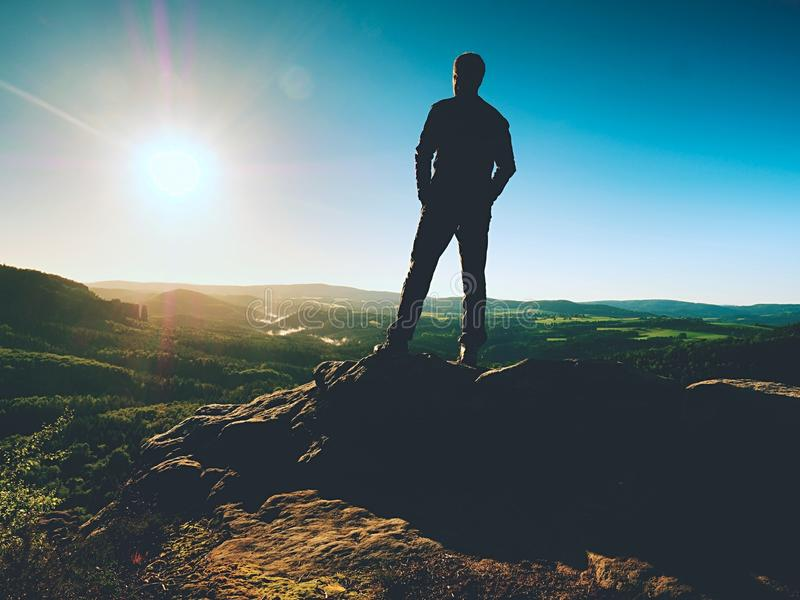 Mężczyzna stojaki na szczycie piaskowiec kołysają oglądać nad doliną słońce piękny moment zdjęcie royalty free