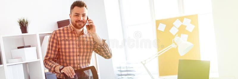 Mężczyzna stojaki w biurze blisko komputerowego biurka, stawiają jego rękę z tyłu krzesła i mówją na telefonie fotografia royalty free