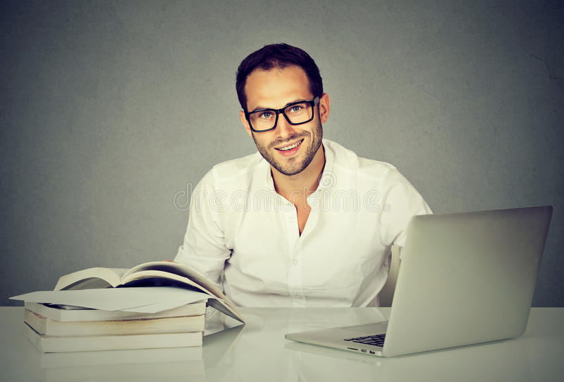 Mężczyzna studencki używa notatnik i czytelnicze książki zdjęcia royalty free