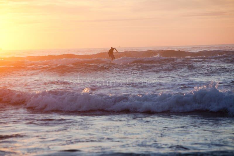 Mężczyzna surfing podczas zmierzchu obrazy stock
