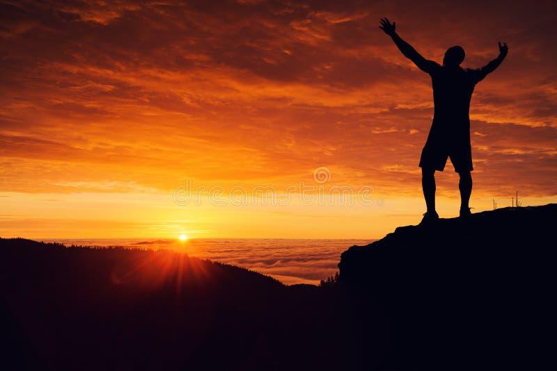 Mężczyzna sylwetka na halnym wierzchołku ogląda zmierzch nad clou obrazy royalty free