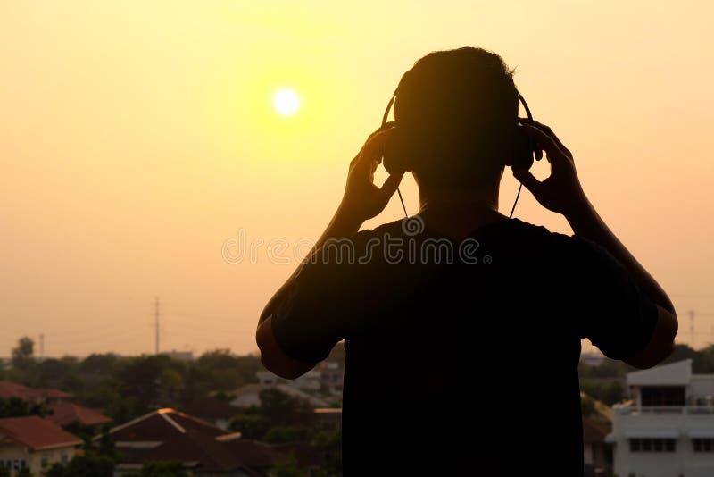 Mężczyzna sylwetka słucha hełmofony obraz royalty free