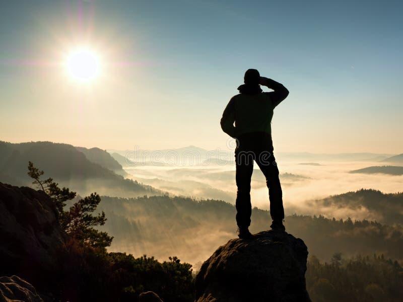 Mężczyzna sylwetki pobyt na ostrze skały szczycie Satysfakcjonuje wycieczkowicza cieszy się widok fotografia stock