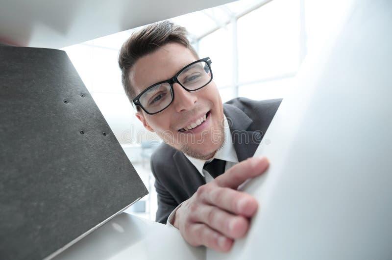 Mężczyzna szuka dokumenty w szkłach przy biurem obrazy stock