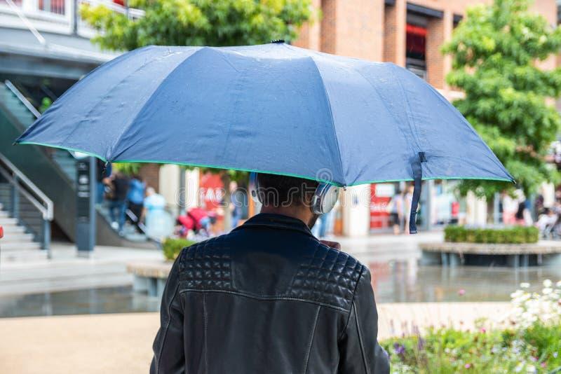Mężczyzna szukający schronienia przed deszczem podczas zakupów zdjęcia stock