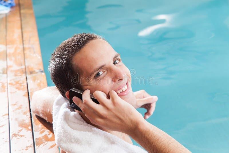 Mężczyzna talkking na wiszącej ozdobie wśrodku basenu fotografia stock
