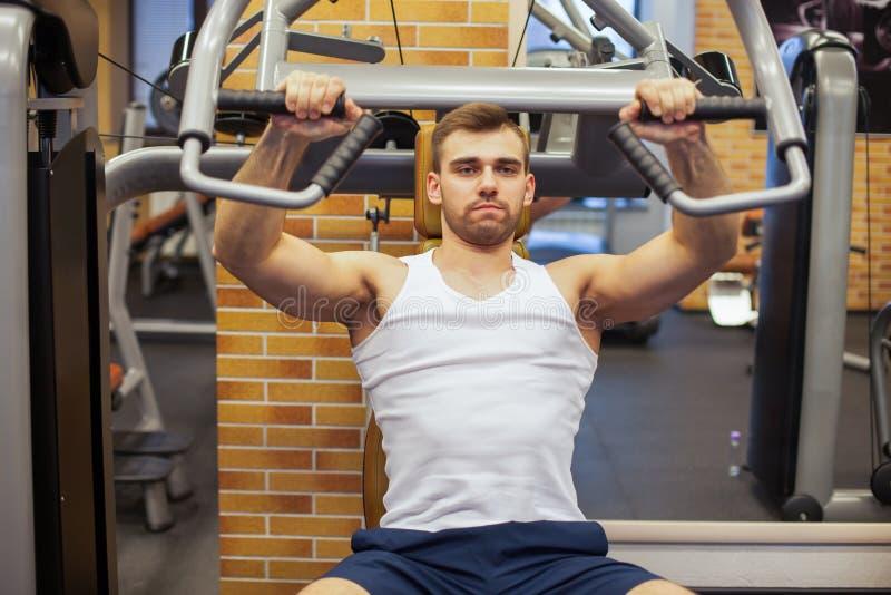Mężczyzna target800_0_ przy gym Sprawności fizycznej atleta robi klatce piersiowej ćwiczy na pionowo ławki prasy maszynie obraz royalty free