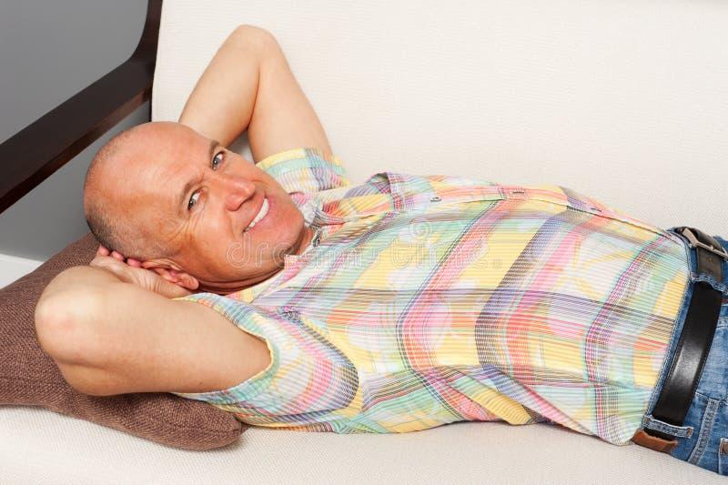 Mężczyzna target1054_0_ na kanapie w domu obrazy stock