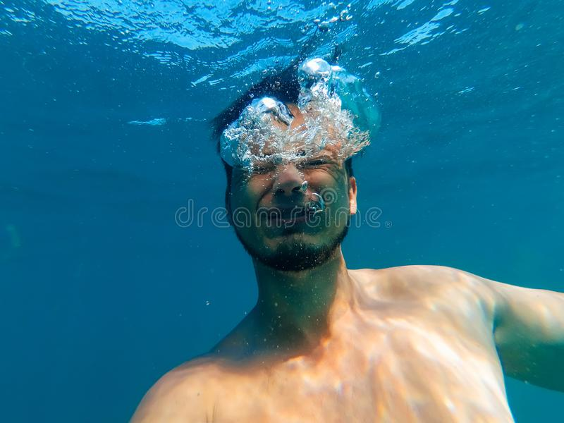 Mężczyzna tonie w głębokim błękitnym morzu pod wodą zdjęcia stock