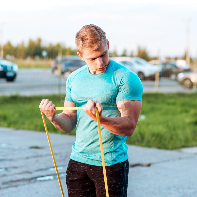 Mężczyzna trenuje jego ręki na gumowych pętlach Zdrowy styl życia atleta Lato styl życia jest plenerowym odtwarzaniem fotografia stock