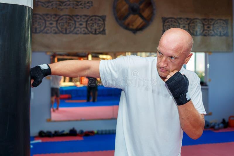 Mężczyzna trenuje przy MMA torba opracowywał garbki fotografia royalty free