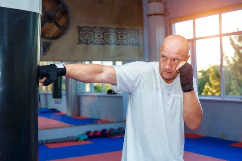 Mężczyzna trenuje przy MMA torba opracowywał garbki obrazy stock