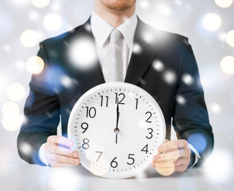 Mężczyzna trzyma ściennego zegar pokazuje 12 fotografia stock