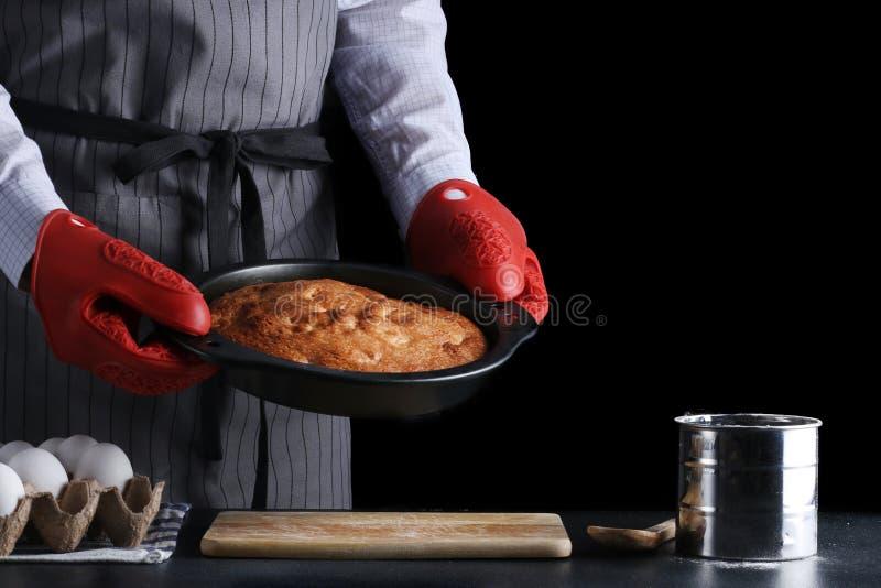 Mężczyzna trzyma świeżo piec kulebiaka na ciemnym tle w fartuchu przepisu od tort lub kulebiak obraz royalty free