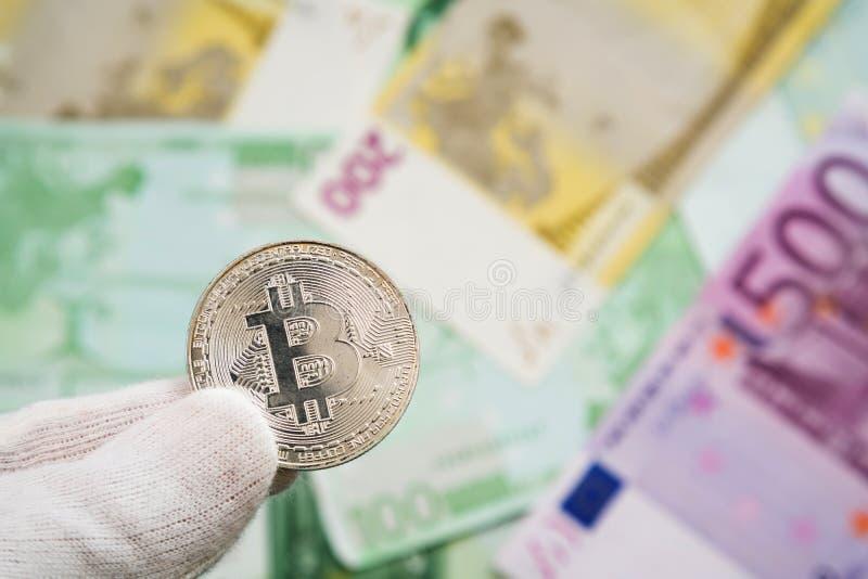 Mężczyzna trzyma Bitcoin monetę między palcami z Euro banknotami w tle w białych cloves Cyfrowej waluta, blokowy ?a?cuch zdjęcia stock