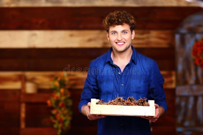 Mężczyzna trzyma drewnianego pudełko z sosnowymi rożkami obraz royalty free
