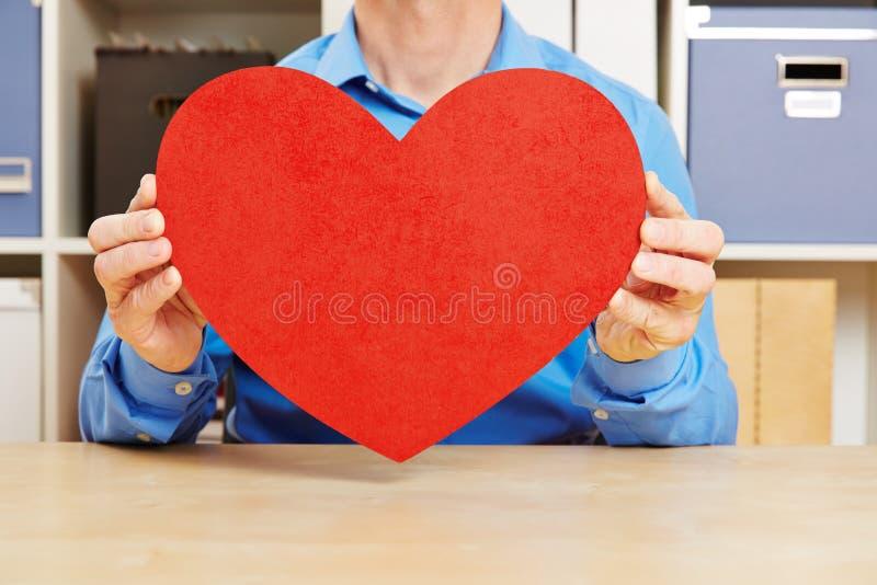 Mężczyzna trzyma dużego czerwonego serce fotografia stock