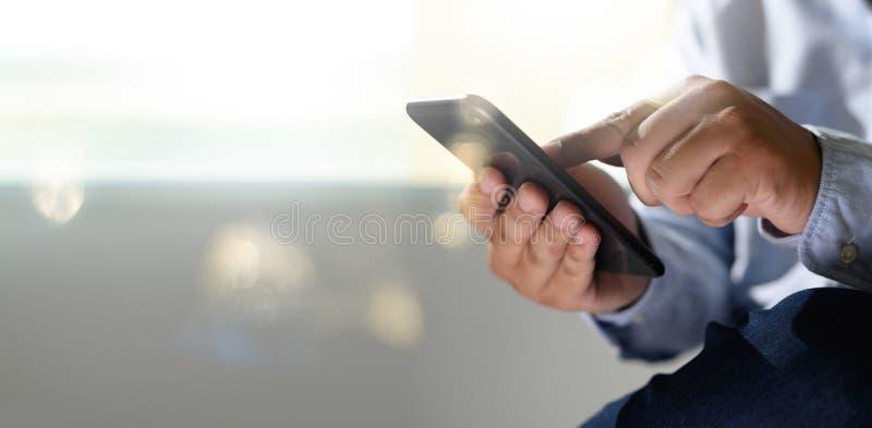 Mężczyzna trzyma en ręki i używa cyfrowego pastylka telefonu komórkowego telefon z puste miejsce kopii przestrzeni piargiem zdjęcia royalty free