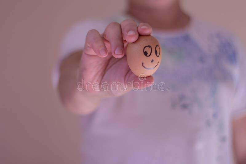 Mężczyzna trzyma jajko z śmieszną twarzą pojęcia tła kosztów właścicieli czarnych konceptualnych domu do domu obraz zarobić repre obraz royalty free