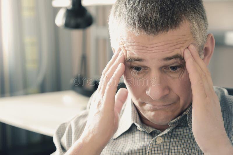 Mężczyzna trzyma jego głowę w jego rękach Problemy w ?yciu osobistym przy prac? i stres Migrena jest konsekwencj? stres zdjęcie royalty free