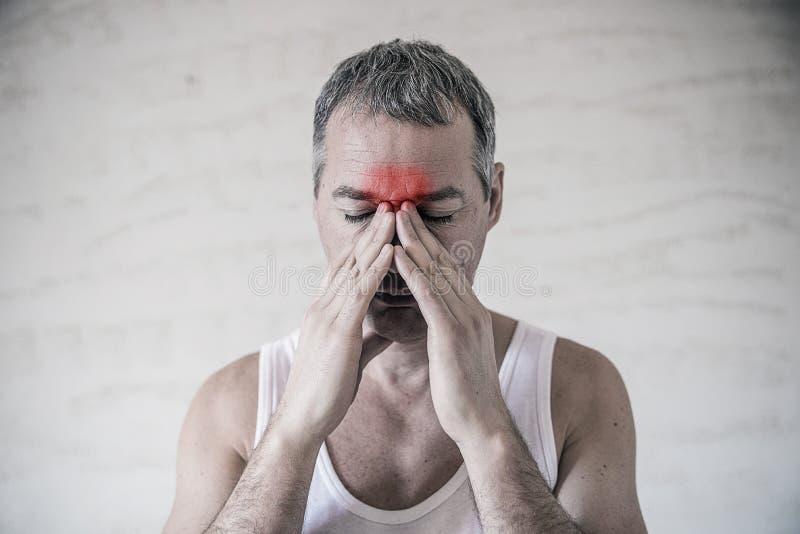 Mężczyzna trzyma jego nosa i sinus teren z palcami w oczywistym pabvious bólu od kierowniczej obolałości w frontowym czoło tereni fotografia royalty free