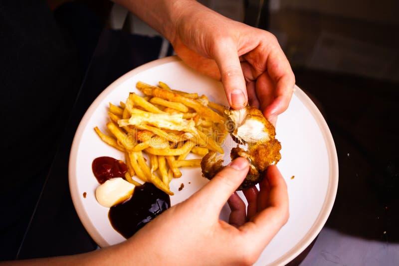 Mężczyzna trzyma kurczaki smażących skrzydła w jego rękach Łasowania mięso z rękami Wyśmienicie posiłek przygotowywający z francu obrazy royalty free