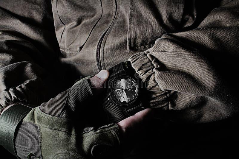 Mężczyzna trzyma militarnego zegarek w kurtce i rękawiczkach obrazy royalty free