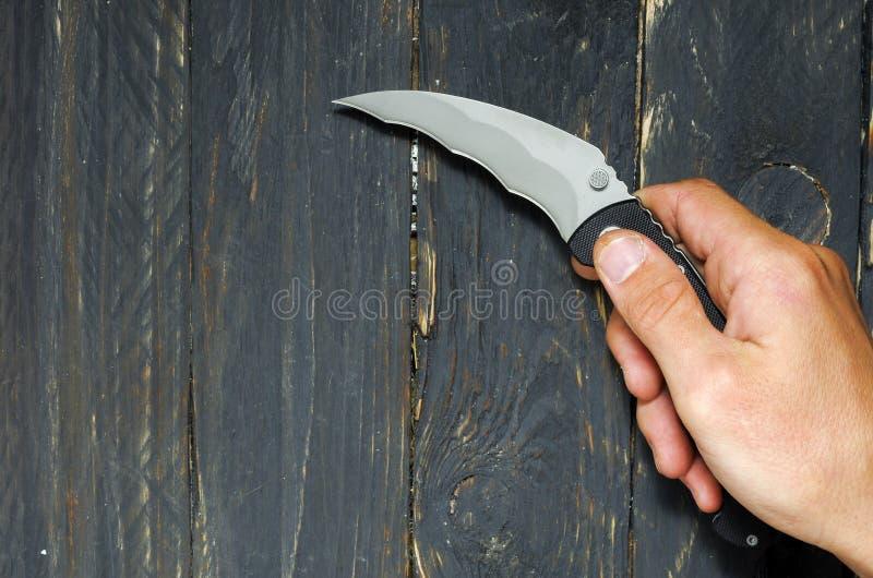 Mężczyzna trzyma nóż w jego prawej ręce Nóż dla ataka zdjęcia stock