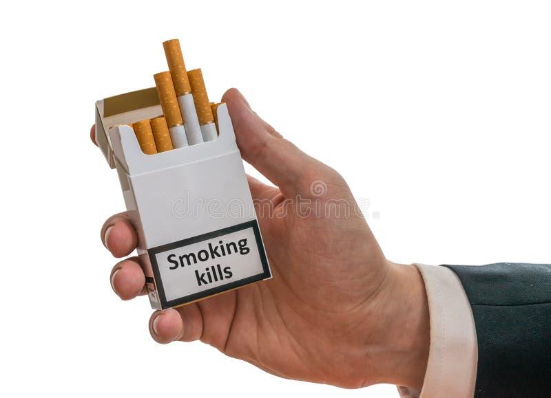 Mężczyzna trzyma papieros paczkę w ręce z ostrzegawczej etykietki dymienia zwłoka zdjęcie stock