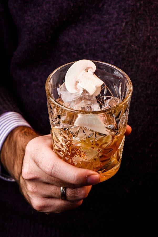 Mężczyzna trzyma pięknego faceted szkło whisky w purpurowym pulowerze dekorował z pieczarkami obraz stock