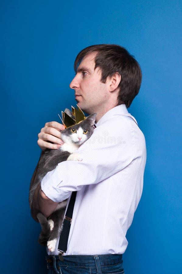 Mężczyzna trzyma popielatego kota w złotej domowej roboty koronie w różowej koszula i czarnych suspenders zdjęcie royalty free