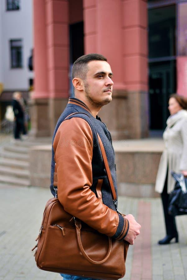 Mężczyzna trzyma rzemienną torbę na jego ramieniu zdjęcia royalty free