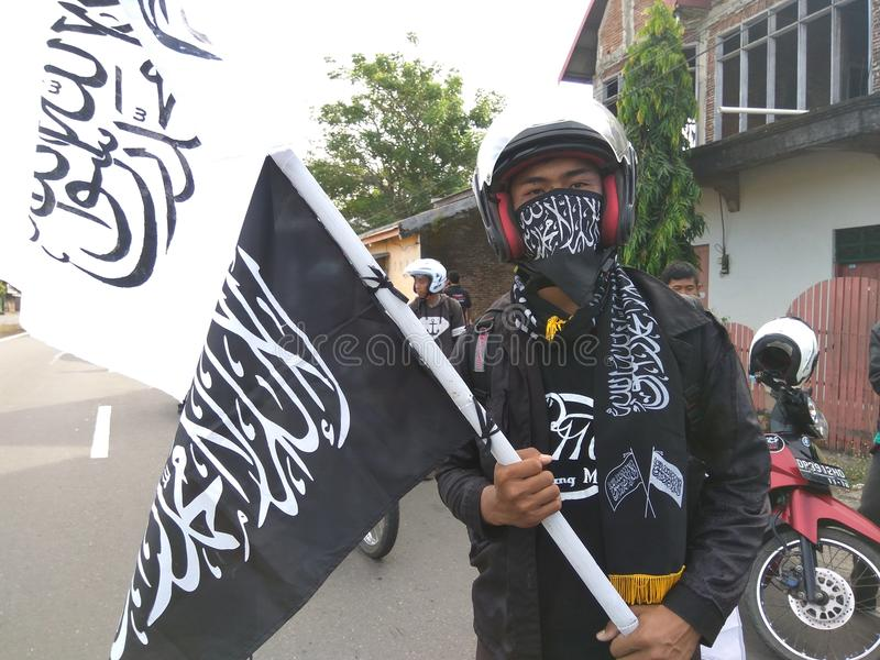 Mężczyzna trzyma sztandar Al liwa, Ar roya i maskowy ar roya obrazy stock