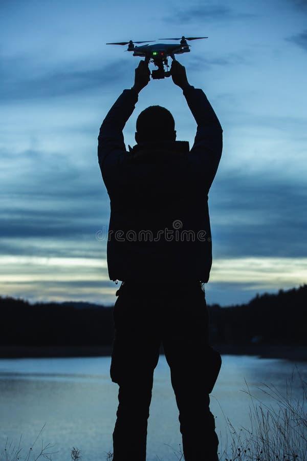 Mężczyzna trzyma trutnia dla powietrznej fotografii Sylwetka przeciw t obraz royalty free