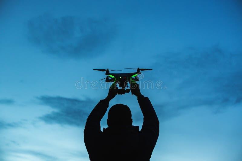 Mężczyzna trzyma trutnia dla powietrznej fotografii Sylwetka przeciw t fotografia royalty free