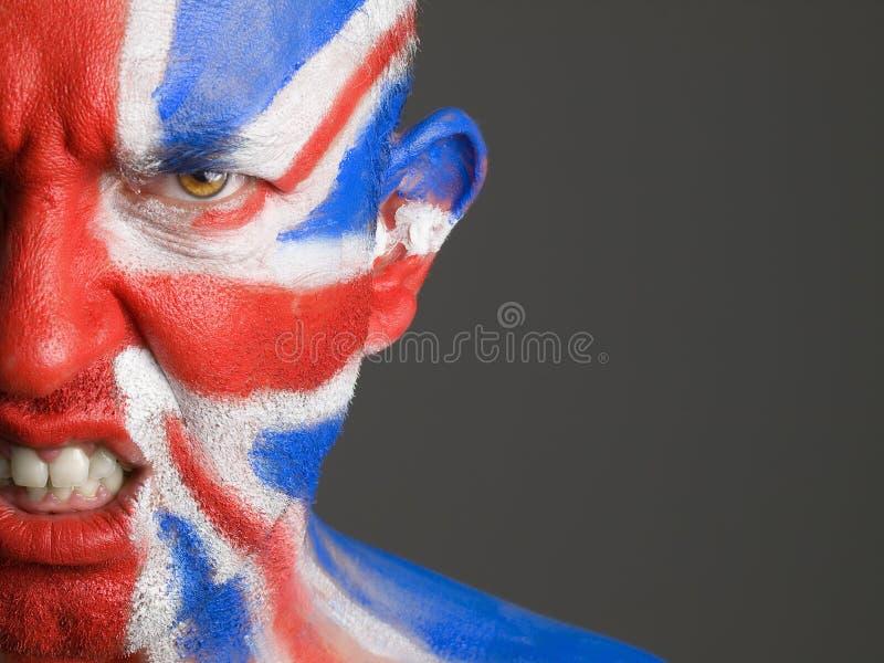 Mężczyzna twarz malował flaga Zjednoczone Królestwo, gniewny wyrażenie