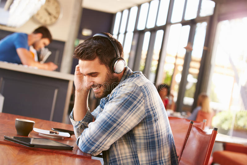 Mężczyzna używa cyfrową pastylkę w sklep z kawą obrazy stock