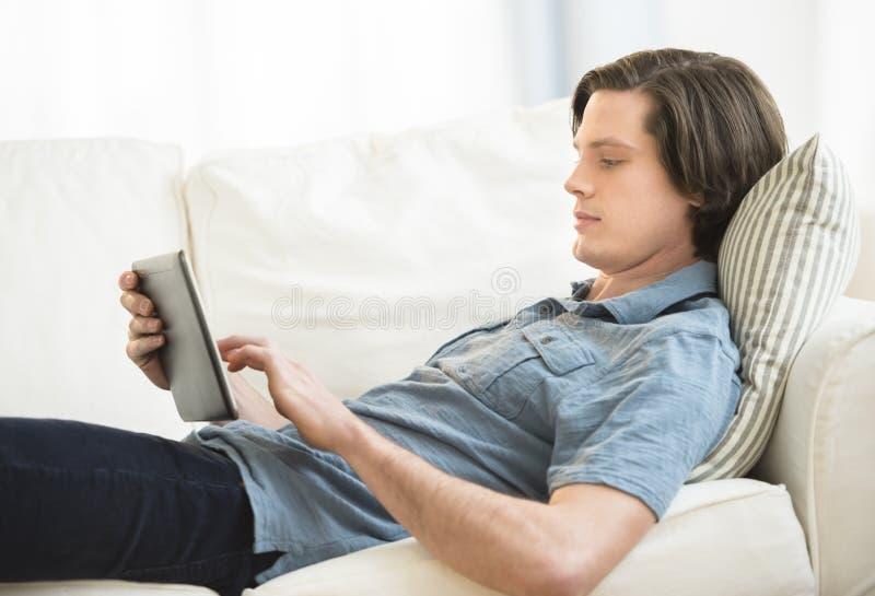 Mężczyzna Używa Cyfrowej pastylkę Podczas gdy Kłamający Na kanapie obrazy stock